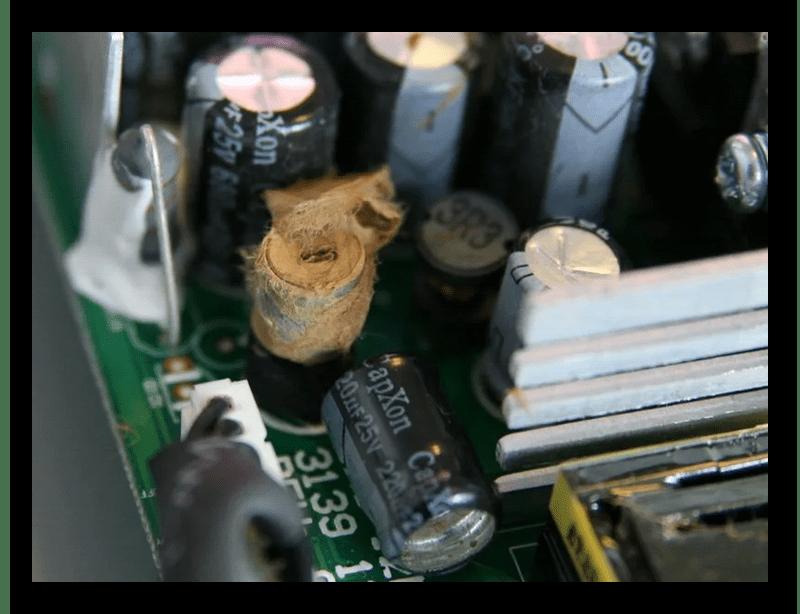 Взорванный электрический конденсатор на материнской плате компьютера
